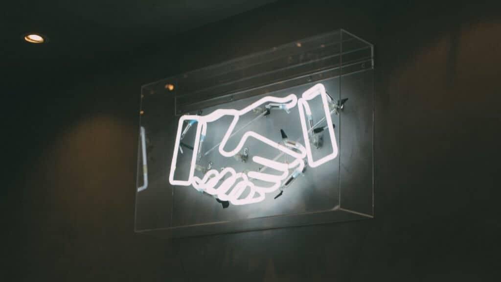 Photo d'une poignée de mains en néons