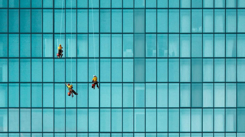 Photo de 3 personnes qui nettoient la façade d'un immeuble