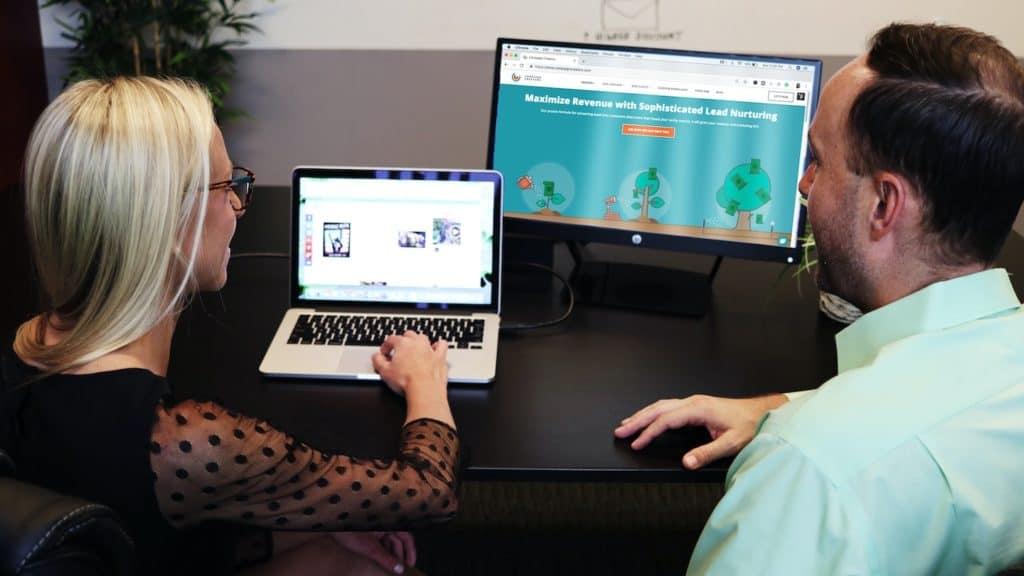 femme et homme comparant ordinateurs