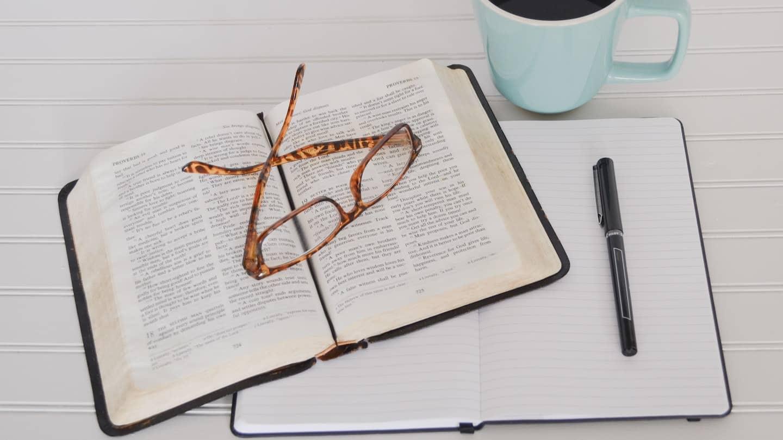 livre, carnet, lunettes et tasse de café