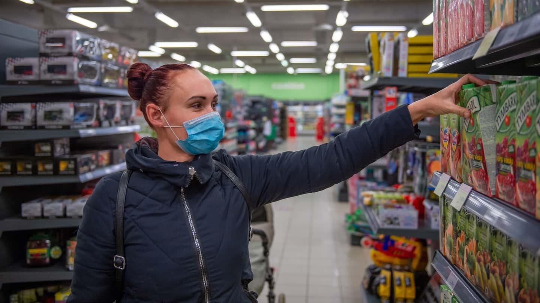 femme selectionnant un produit dans un rayon de supermarché