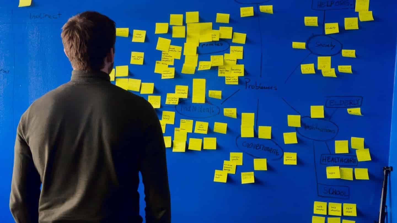 Personne examinant des post-it au mur : brainstorming